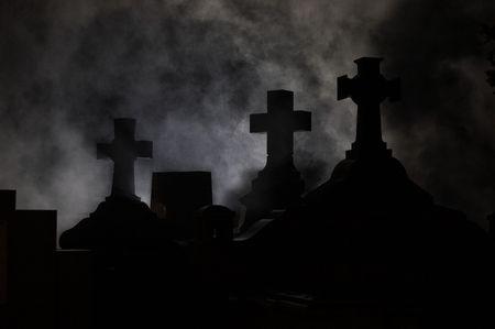 mortal: Headstone cross in Graveyard at night.