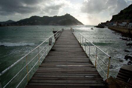 san sebastian: Footbridge of  Nautical Club in San Sebastian, Spain. Santa Clara Island and Igueldo Castle in background.