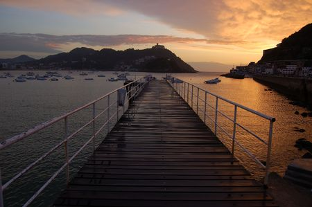 Footbridge of  Nautical Club in San Sebastian at twilight. Spain. Santa Clara Island and Igueldo Castle in background.
