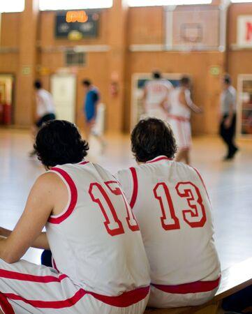 amateur: Baloncesto aficionado. Dos jugadores esperando en el banquillo Foto de archivo