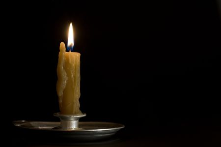 Antique metal candlestick with burning candle on black background. Stock Photo