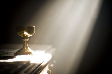 holy eucharist: Gold chalice in altar with a ray of divine light in a church Stock Photo