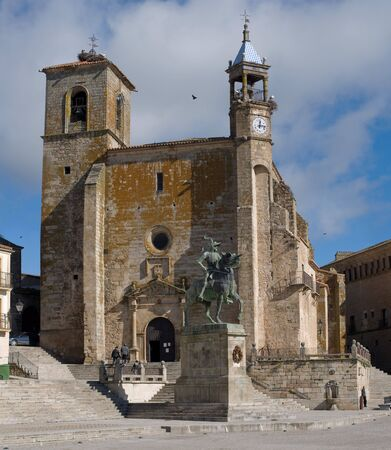 conqueror: Statue of Francisco Pizarro (Spanish explorer and conqueror of Peru) and the Church of St. Martin in Mayor Square of Trujillo. Caceres, Spain. Stock Photo
