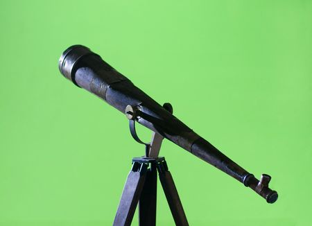 tripod mounted: Antique wood telescope mounted on a tripod isolated on green Stock Photo