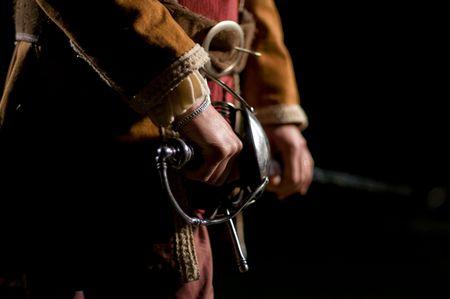 European Musketeer o Swordsman over a Black Background. Sword handle detail. Stock Photo