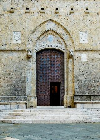 siena: Monte dei Paschi door of Palazzo Spannocchi in Piazza Salimbeni  Siena, Italy