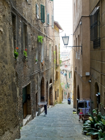little town: Siena street with typical antique houses  Siena, Italy Stock Photo