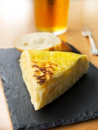 Typical spanish pincho de tortilla de patatas in slate plate Stock Photo