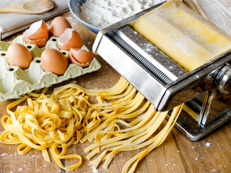 Fresh pasta cutting in machine. Fettuccini homemade. Stock Photo
