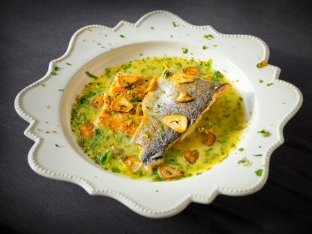san sebastian: Pan-fried sea trout in green sauce with fried garlic slices.
