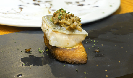 low temperature: Typical spanish codfish pincho cooked at low temperature in slate plate  Stock Photo