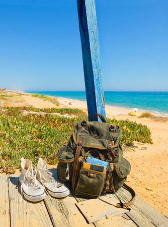 taking a break: Backpack and shoes on the porch of a wooden hut next to the shore of a European beach. Backpacking traveller taking a break in a tour through Algarve, Portugal. (Tavira beach in Tavira island) Stock Photo
