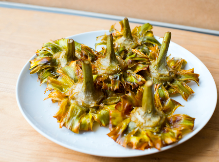 Roman fried artichokes (jewish style) with flakes of sea salt on a wooden table. Stock Photo