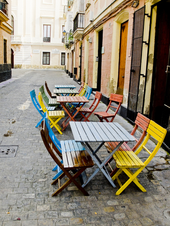 cadiz: Colorful chairs in a typical street of Cadiz old town. Andalusia, Spain. Stock Photo