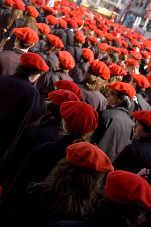 berets: Irun Spain June 30 2007. Thousands of Citizens wearing uniforms and Organised into Their respective companies each with barmaid and wearing red berets. The boast of San Marcial in Irun. Guipuzcoa SpainThe boast of San Marcial in Irun commemorates the vict Editorial
