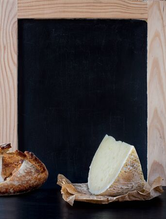 carte: Soft cheese wedge and piece of rustic bread loaf in front of blank old blackboard carte.