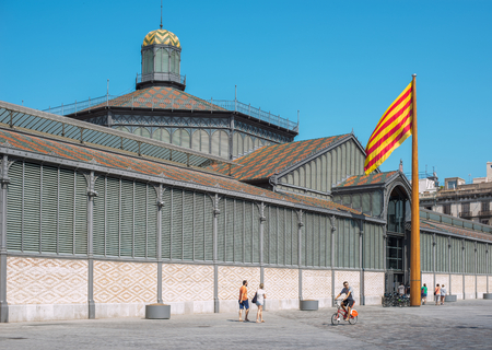 chaired: Cyclist and walkers in front of the principal facade of El Born market or Mercat del Born, chaired by the flag of Catalunya.This building is one of the most representative Modernisme in Catalan architecture located in the Born district. Barcelona, Catalon Editorial