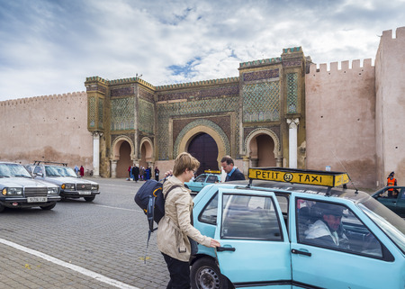 bab: Woman taking a Petit Taxi front of The Bab Mansour in the medina of Meknes. This gate is one of the most beautiful works of Moulay Ismail and the largest in Moroccogetting Editorial