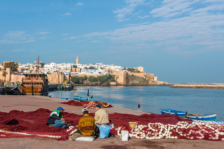 fishermans net: Fishermans in Rabat fixing fishing net fishing port, located in the river Bou Regreg at the mouth of the Atlantic Ocean. Kasbah of the Udayas in background. Editorial