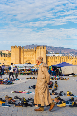 exterior shape: People with djellaba walking in market of Bab Chorfa at sunset, view from Bou Jeloud square. Bab Chorfa is a gate to ancient Fez El Bali Medina. Fez, Morocco. North Africa.