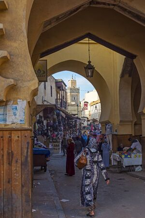 north gate: Moroccan citizens in a quotidian scene in Semmarin Medina Gate of Fez El Jdid with Jama El Hamra mosque minaret in background. Fez, Morocco. North Africa.