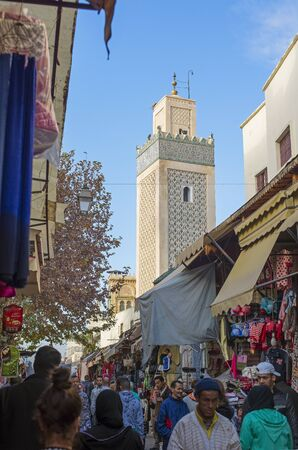 rue: Moroccan citizens in a quotidian scene in Grand Rue de Fez El Jdid with Jama El Hamra mosque minaret in background. Fez, Morocco. North Africa. Editorial