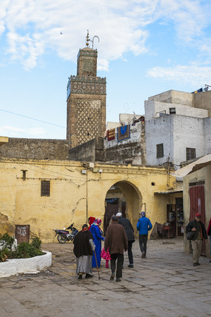 bab: Moroccan citizens in a quotidian scene in Fez El Jdid with bab Moulay Abdellah mosque minaret in background. Fez, Morocco. North Africa. Editorial