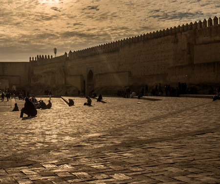 bab: Moroccan citizens in a relaxation quotidian scene in Bab Mahrouk walls at sunset, view from Bou Jeloud square. Bab Mahrouk is a gate to ancient Fez El Bali Medina. Fez, Morocco. North Africa.