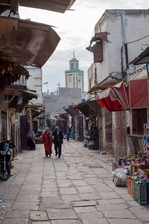fez: Moroccan citizens in a quotidian scene in Fez El Jdid with Mausolee Moulay Abdellah mausoleum minaret in background. Fez, Morocco. North Africa. Editorial