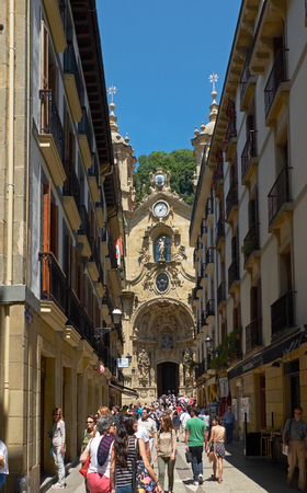 vieja: People walking in Nagusia street with The Basilica of Saint Mary of Coro in background, located in the Parte Vieja Old Town. Basque Country, Guipuzcoa. Spain.