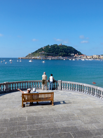 san sebastian: Senior couple watching the Concha bay and Santa Clara island in Kontxa Pasalekua balcony. San Sebastian, Guipuzcoa. Spain Editorial