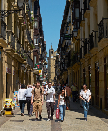 san sebastian: People walking in Narrika street with The San Vicente Church in background, located in the Parte Vieja Old Town. Basque Country, Guipuzcoa. Spain.