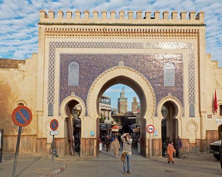 bab: Tourist taking photos and people with djellaba walking in Bab Bou Jeloud. The blue gate is a gate to ancient Fez El Bali Medina. Fez, Morocco. North Africa.