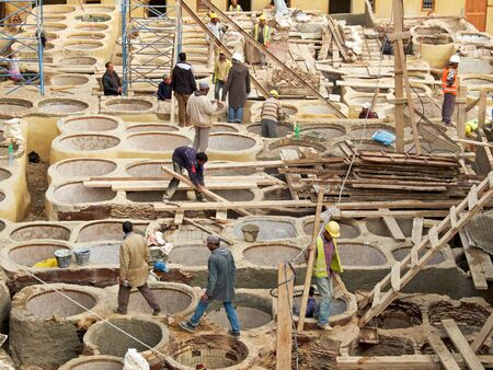 building structures: Laborers working on rehab in the Chouwara leather tannery in the Fes El Bali Medina.The restoration works of the tannery have focused on building structures and walls, ceilings, tanks, electricity grids and a waste collection system to limit pollution wit Editorial