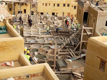 laborers: Laborers working on rehab in the Chouwara leather tannery in the Fes El Bali Medina.The restoration works of the tannery have focused on building structures and walls, ceilings, tanks, electricity grids and a waste collection system to limit pollution wit Editorial