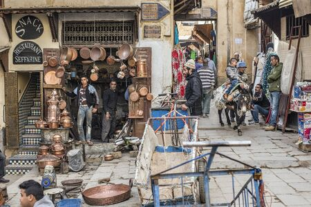 fez: Artisans and Citizens in Place Seffarine, metal souk square, in a quotidian scene. Place Seffarine, Fez El Bali Medina. Fez, Morocco. North Africa.