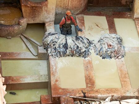 obligated: Laborer working in Chouwara leather tannery in the Fes El Bali Medina.Fez is famous for its leather goods and the sight of tanneries has become a obligated visit. Fez El Bali, Morocco, Africa. Editorial