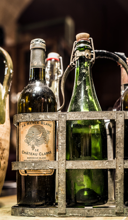 vinery: Antiques french wine bottles from Bordeaux in a vintage metal bottle carrier. Aquitaine, France.