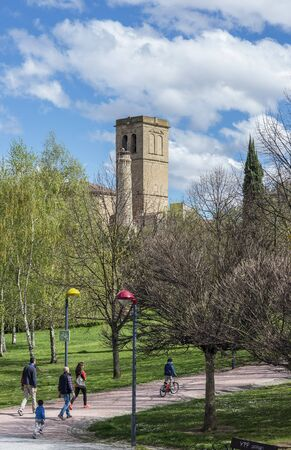 real renaissance: Logrono, Spain - April 10, 2016. A family walking in Park of the river Ebro with bellower of Santiago el Real church. Logrono, La Rioja. Spain.