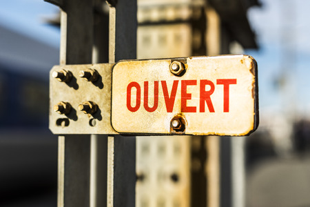 overt: Overt (open in french) metal rusty sign at sunset. Stock Photo