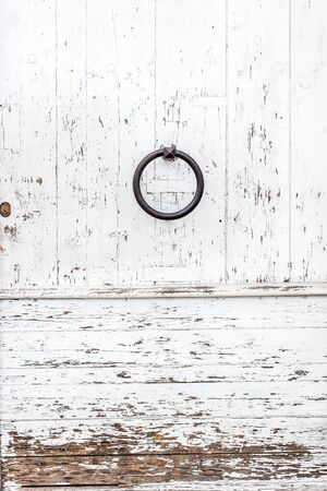 chipped: Weathered white wooden door with a metal ring knob and rusty lock textured with white paint chipped and peeling. Stock Photo