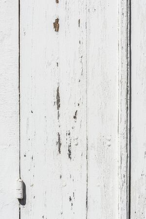 chipped: Weathered white wooden door with hinges textured with white paint chipped and peeling.