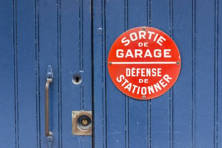 not painted: Sortie de garage, Defense de stationer (No parking in french) sing on a garage blue wooden door.