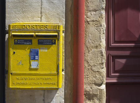 postes: Saint Jean de Luz - Ciboure, France - May 21, 2016: French yellow metal mailboxes on stone wall in a street of Aquitaine. France.