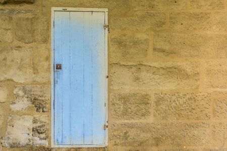 rusty: Weathered blue wooden door with a metallic rusty lock textured with paint chipped and peeling.