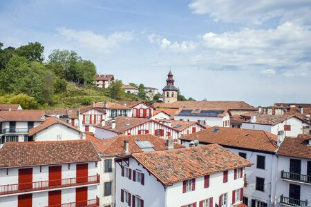 aquitaine: View of the rooftops of typical buildings and belfry of Saint-Vicent church of Ciboure in Basque country. Aquitaine, France.