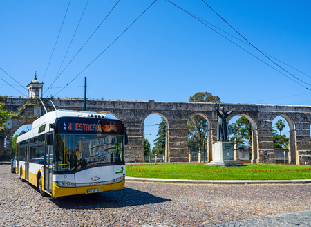 patrimony: Typical bus of Coimbra crossing in front of the statue of John Paul II and Pope Aqueduto de Sao Sebastiao the aqueduct. Portugal.