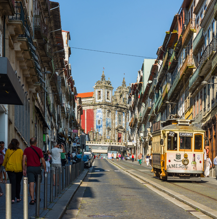 proto: Tram crossing street Rua 31 de Janeiro With Igreja de Santo Ildefonso church in background.