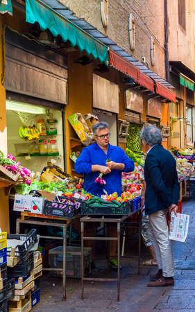 greengrocer: Man buying vegetables in a greengrocer stall in the Quadrilatero, market zone of Bologna. Emilia-Romagna. Italy.