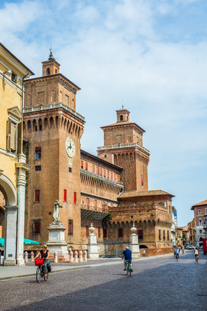 martiri: Cyclists crossing street Corso Martiri della Liberta With Estense castle in background. Ferrara, Emilia-Romagna. Italy.